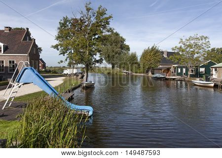 Slide and natural swimming pool in the village Ottoland in the Netherlands
