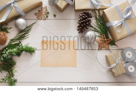 Creative diy hobby background. Handmade making christmas present, box in craft paper with satin silver ribbon. Top view of white wooden table with copy space on sheet of paper, decoration of gift.