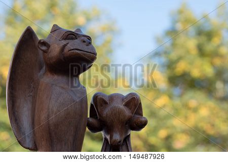 Wooden carved figures of fabulous bat / vampire and sheep with natural fall background in the back from market stand at the fall folk festival - September 24 2016, Heidelberg, Germany
