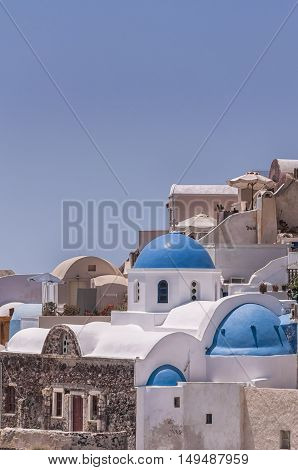 A view of a blue domed church from Oia on the greek isle of Santorini.