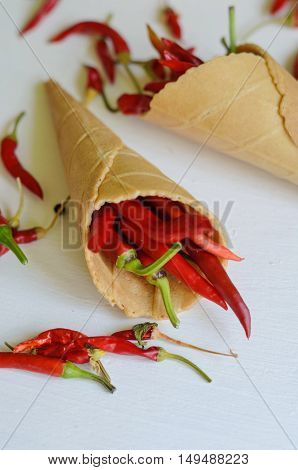 Red hot chili peppers in sugar waffle cones on white background copy space for text