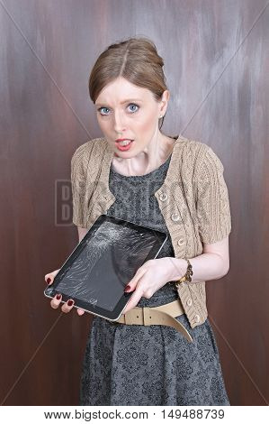 Young woman with shocked face expression over broken tablet display
