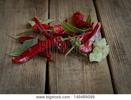 red pepper and bay leaves on wooden background