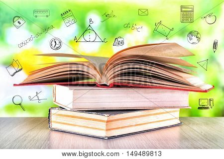 Stack of books on wooden table. Icons on blurred green background. Knowledge concept.