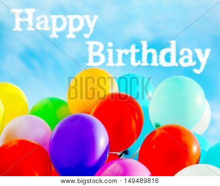Happy Birthday text and colorful balloons on blue sky background