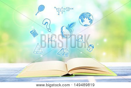 Book on wooden table. Icons on blurred green background. Knowledge concept.