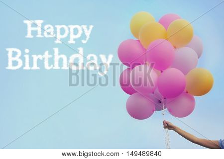 Happy Birthday text and woman hand holding air balloons on sky background