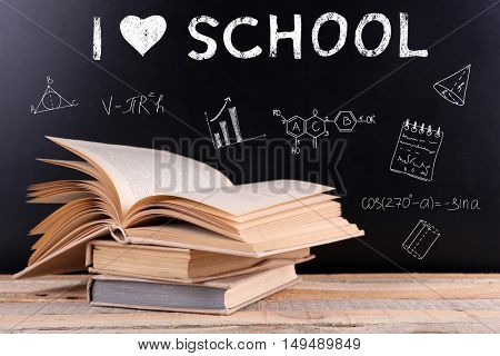 Stack of books on wooden table. Text I LOVE SCHOOL and icons on blurred blackboard background. Knowledge concept.
