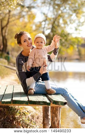 Smiling mother holding baby girl 1 year old wearing knitted casual clothes aitting in autumn park. Looking at camera. Motherhood.