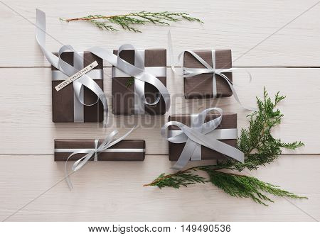 Lots of gift boxes and fir tree branches on white wood background. Stylish modern presents in dark paper decorated with satin ribbon bows. Christmas and winter holidays concept, top view, flat lay
