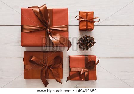Lots of gift boxes and pine cone on white wood background. Stylish modern presents in brown paper decorated with satin ribbon bows. Christmas and winter holidays concept, top view, flat lay