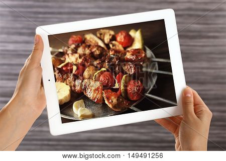 Female hands holding tablet on blurred wooden background. Photo of food on tablet screen.