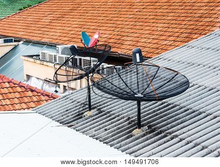Two satellite dish set on tile roof.