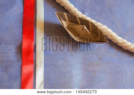 USA holiday, happy Columbus day paper boat on blue background and ribbons decorations