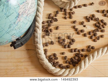 Happy day of conception of Columbus. A globe, a rope, coffee beans on a wooden Board.