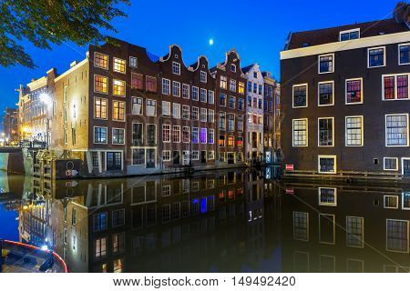 Beautiful typical Dutch houses at the Amsterdam canal at night, Holland, Netherlands.