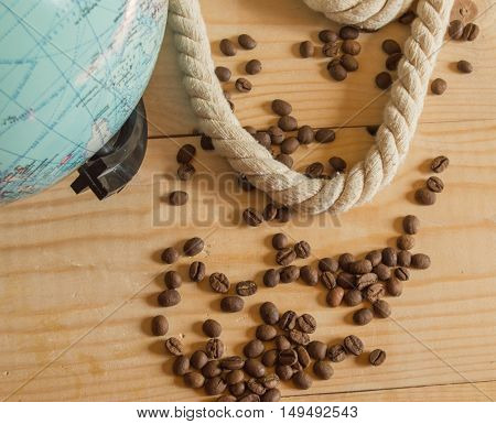 Happy day of conception Columbus. A globe, rope, coffee beans on wooden Board.