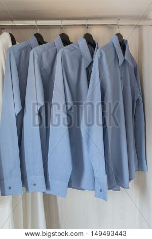 Row Of Blue Color Shirts Hanging On Rail