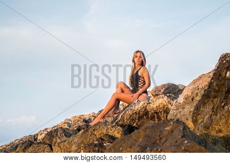 Sexy young woman meets the sunrise on the rocks near the sea
