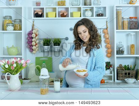 beautiful pregnant woman with  milk at kitchen