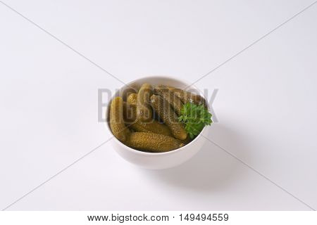 bowl of pickled cucumbers on white background