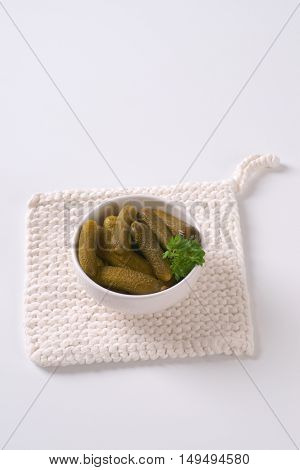 bowl of pickled cucumbers on white table mat