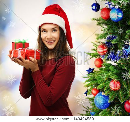 Beautiful happy woman with gifts and decorated Christmas tree on blurred lights background. Christmas holiday concept.