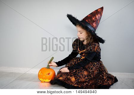 The beautiful girl of 8-9 years in image the evil fairy. The girl has dressed up by Halloween. In hands at her pumpkin with a candle inside - Halloween symbol.