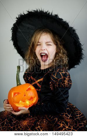 Halloween. Girl portrays evil sorceress.She is wearing black-and-orange dress and hat. In hands is her pumpkin - Jack o lantern