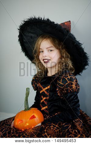 The beautiful girl of 8-9 years in image is the evil fairy. The girl has dressed up for Halloween. In hands is her pumpkin with a candle inside - Halloween symbol.