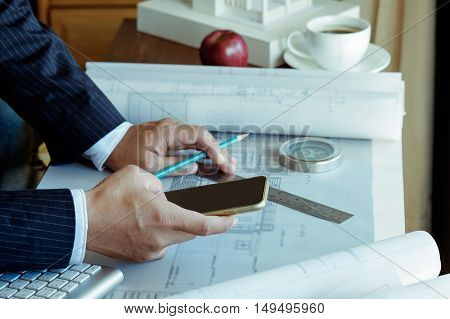 Architects using smart phone while Discussing Plan in office.