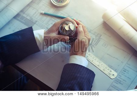 Architects holding coin jar while Discussing Plan in office.