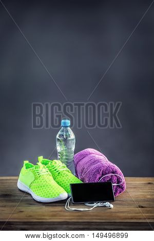 Pair of yellow green sport shoes towel water smart phone and headphones on wooden board. In the background forest or park trail.Accessories for running sport.
