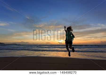 Woman Traveller Happy Jumping On The Beach With Sunrise, Image Of Lifestyle Freedom Life Concept