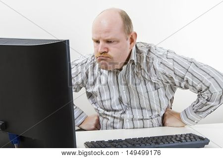 Angry businessman with hands on waist looking at computer on desk in office