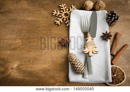 Vintage or rustic christmas table setting from above. Cutlery on linen napkin on rustic wooden background - country style. Selective focus space for text.