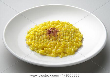 Saffron risotto dish isolated on grey plane