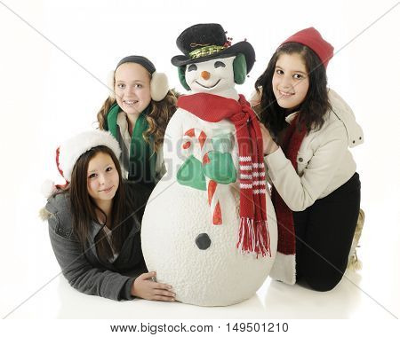 Three young teens happily posing with a Christmas snowman.  On a white background,.