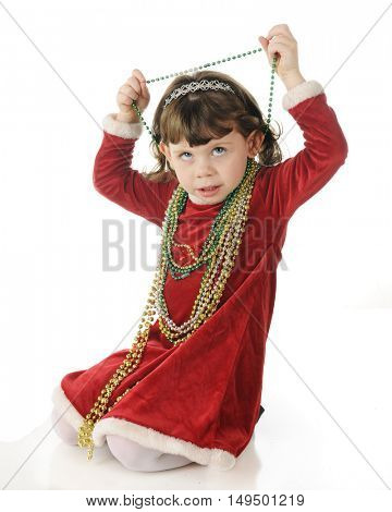 An adorable dressed up preschooler looking up as she removed strands of Christmas beads from around her neck.  On a white background.