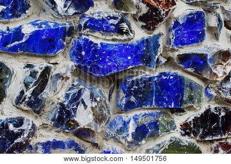 Abstract wallpaper texture of real walls, bright color. Blue color, with colored stone and glass in a concrete gray wall.