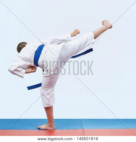 On the red and blue tatami karate athlete beats kicking