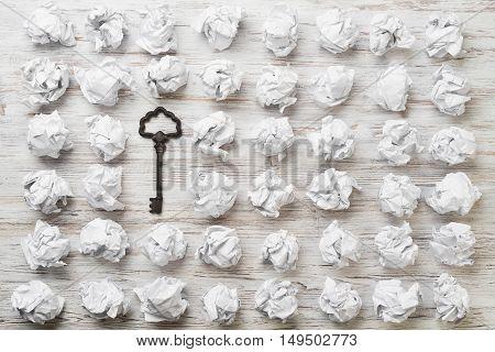Vintage key among many balls of crumpled white paper