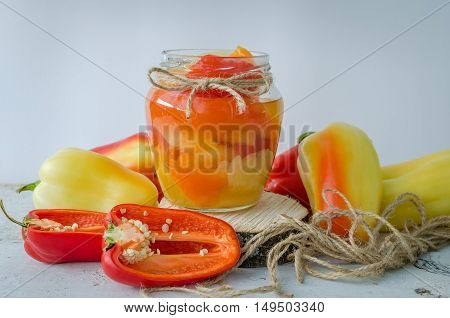 Bell pepper preserved in a glass jar with fresh peppers on white wooden background. Homemade marinated in oil red pepper. Glass jar with conserved roasted sweet paprika. Selective focus.