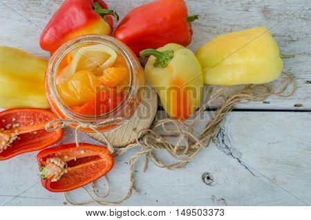Bell pepper preserved in a glass jar with fresh peppers on white wooden background. Homemade marinated in oil red pepper. Glass jar with conserved roasted yellow and red paprika. Top view. Copy space.