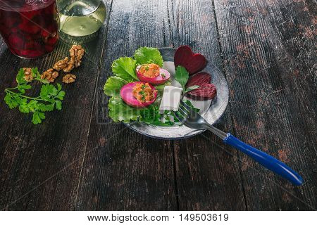 Pickled bettroot eggs with spicy filling served with salad leaves and beet hearts