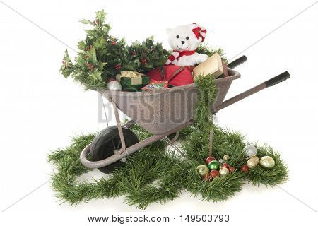 A rustic wheelbarrow surrounded with garland and bulbs and filled with holly and gifts.  On a white background.