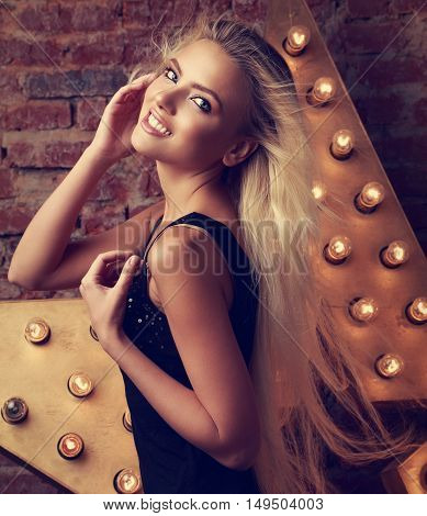 Young Smiling Woman Posing With Long Blond Hair On Star And Brick Wall Background. Toned Closeup Por