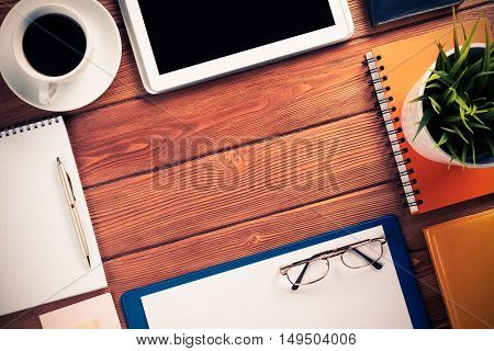 Still life photo of tablet, notepad, coffee, glasses and other items on wooden table.
