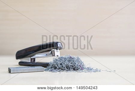 Closeup pile of used staples with blurred black stapler and staples office equipment on blurred wood desk and wall in office room textured background under window light