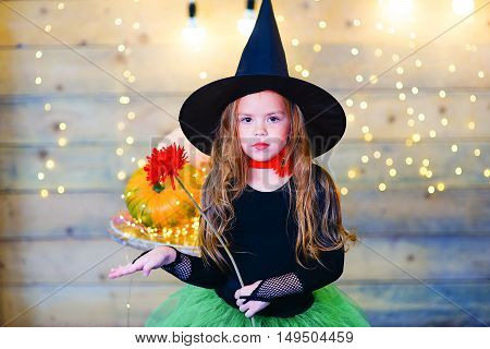 Happy witch children during Halloween party playing around the table with pumpkins